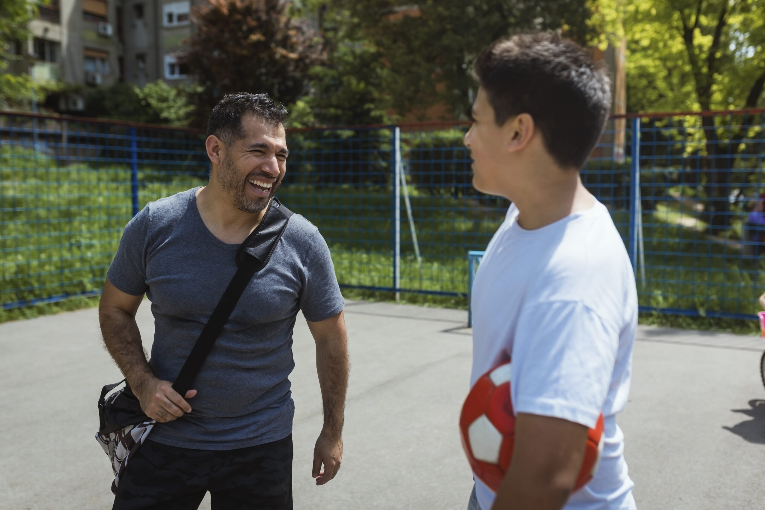 Father and son spending quality time together.Playing soccer in public park.